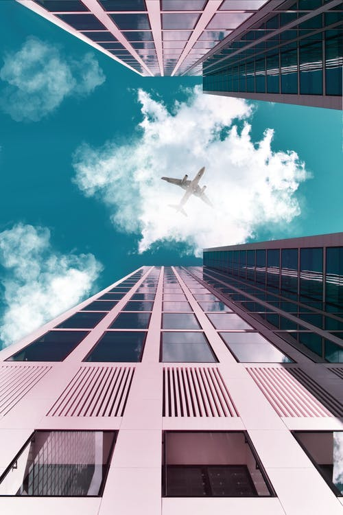 An Airplane Flying Over The Buildings