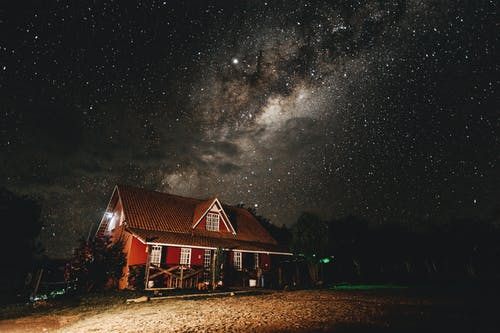 Brown Cabin Photo during Starry Nighttime