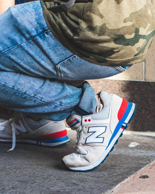 Person Wearing White-and-blue New Balance Sneakers