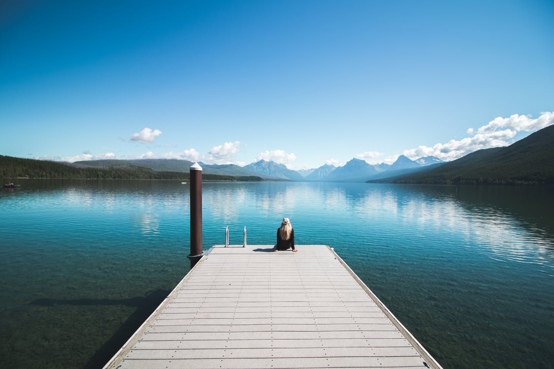 Back View Photo of Woman Sitting on Wooden Dock