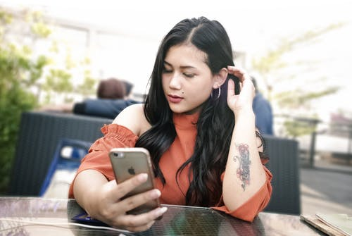 Selective Focus Photo of Woman Using Smartphone While Sitting By Table