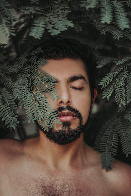 Topless Man Standing Beside Green Plant