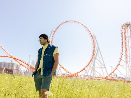 Man Wearing Blue Button-up Sleeveless Vest and Yellow Shirt Standing Near Roller Coaster