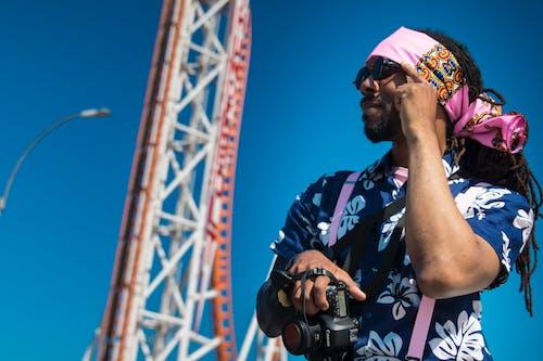 Man Standing Near Park Roller Coaster