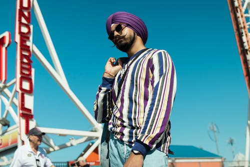 Photo of Man Wearing Striped Long Sleeved Shirt and Purple Turban