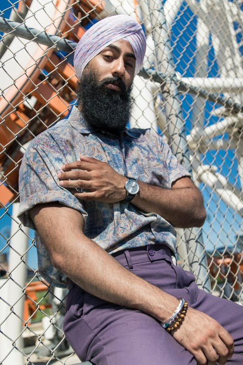 Man Wearing Purple Turban and Gray Polo Shirt With Purple Pants Laying on Gray Cyclone Fence