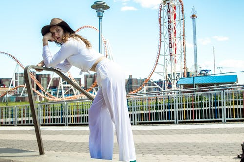 Photo of Woman in White Outfit Leaning Forward on Metal Railing with Amusement Park in the Background