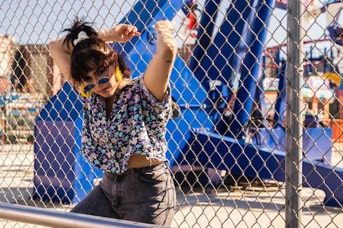 Woman Leaning Beside Metal Fence