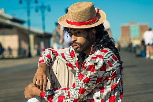 Man Sitting on Concrete Ground Wearing Hat