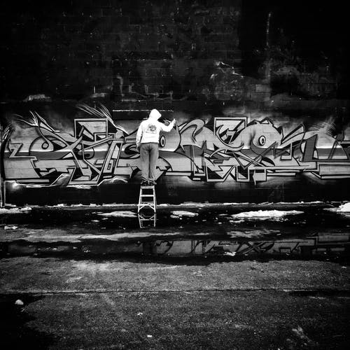 Grayscale Photo of Person Doing Graffiti