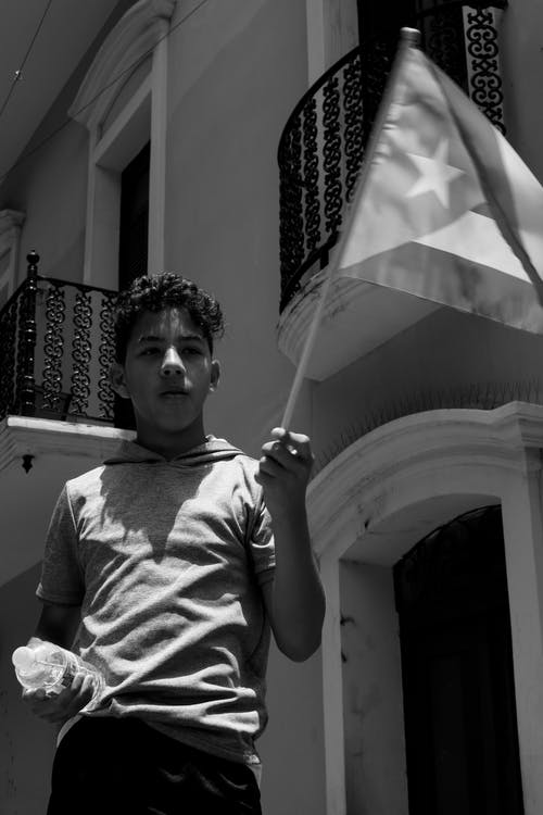 Grayscale Photo of Teenage Boy Holding Cuban Flag