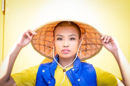 Portrait Photo of Woman in Bamboo Hat Posing In Front Of Yellow Door