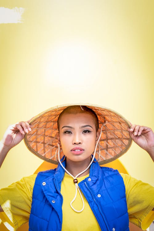 Portrait Photo of Woman in Bamboo Hat Posing In Front Of Yellow Wall