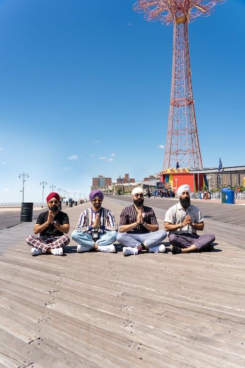 Four Men Sitting on Boardwalk