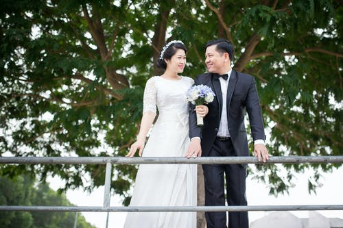 Photo of Couple Smiling While Standing Near Handrail