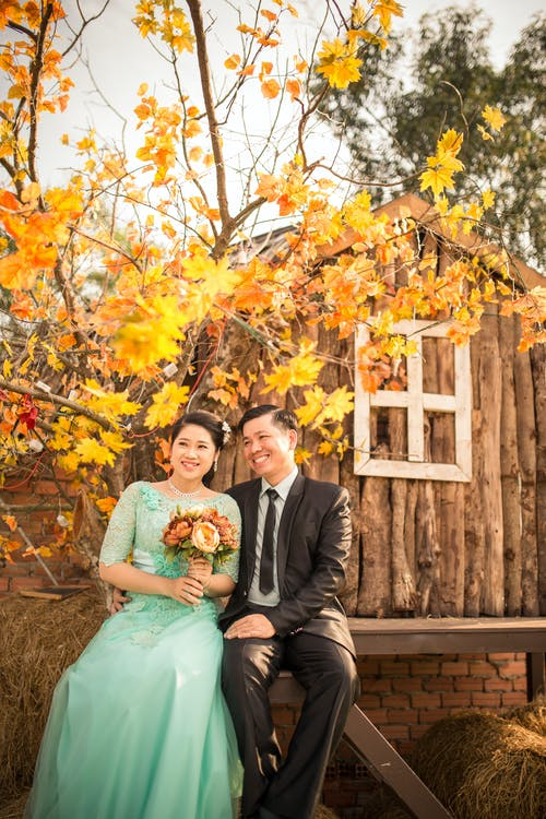 Bride and Groom Sitting on Wooden Chair