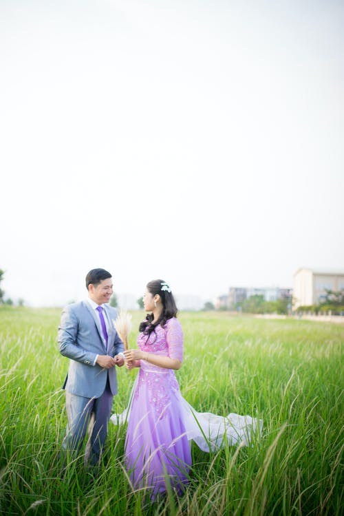 Photo of Couple Standing on Grass Field