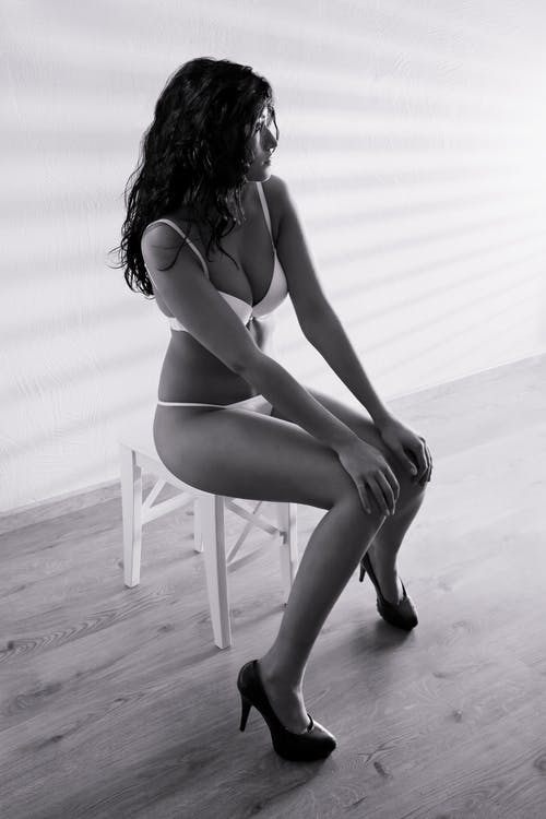 Woman in White Bra and Panty Sitting on Chair