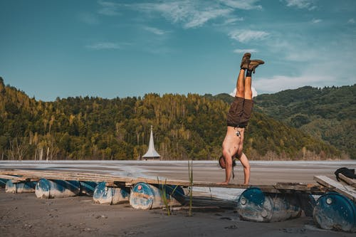 Man Doing Handstand on Wooden Planks