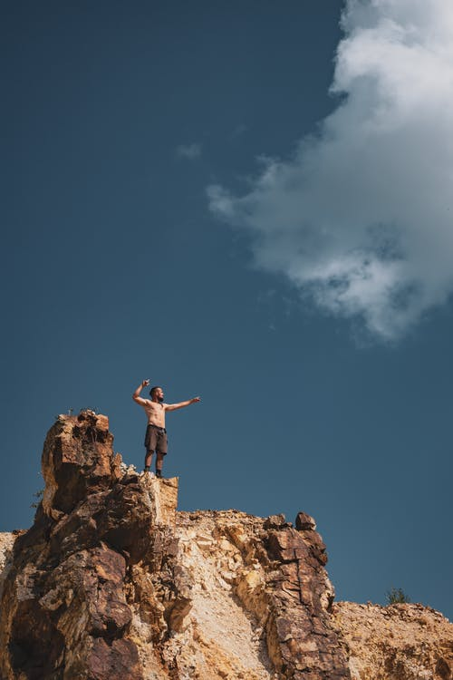 Topless Man Standing on Cliff