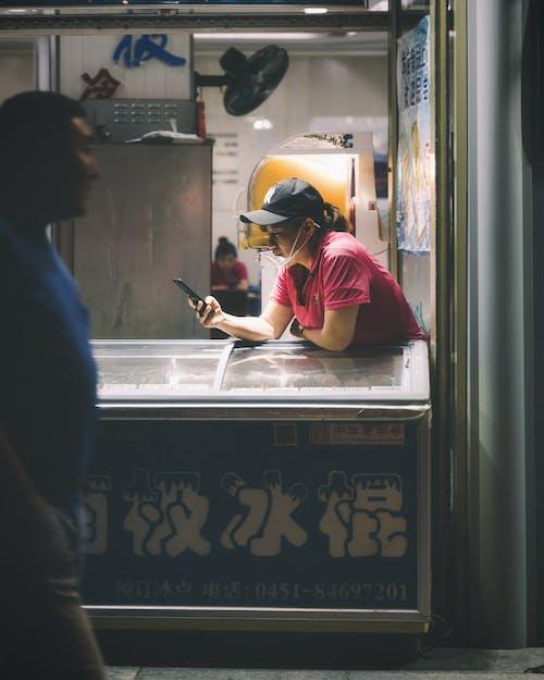 Základová fotografie zdarma na téma asiaté, chytrý telefon, dospělý, kšiltovka