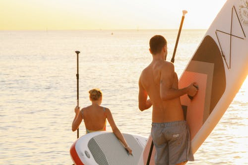 Photo of Man and Woman Holding a Paddleboard