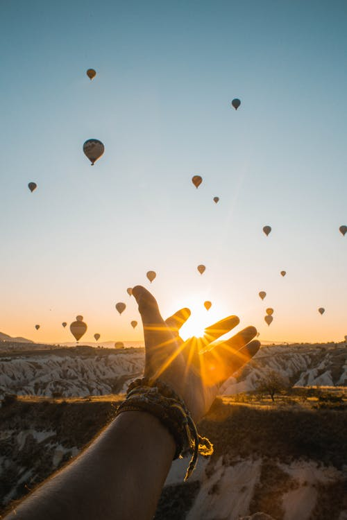 Photo of Person's Hand Across Flying Hot Air Balloons During Golden Hour