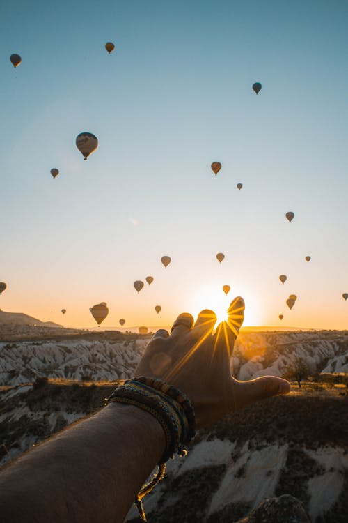 Photo of Person's Hand Across Flying Hot Air Balloons