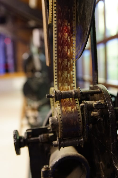 From above of vintage movie camera with film roll on metal feed spool near window in cinematography studio