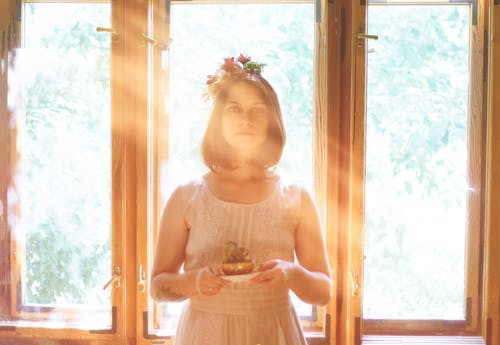 Woman Holding A Plant With Sunlight Through The Window