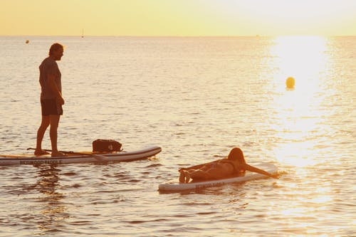Man and Woman Riding Paddleboards