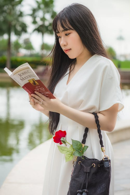 Woman Wearing White V-neck Dress While Holding Book