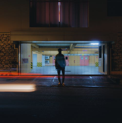 Man Standing Beside Building at Night