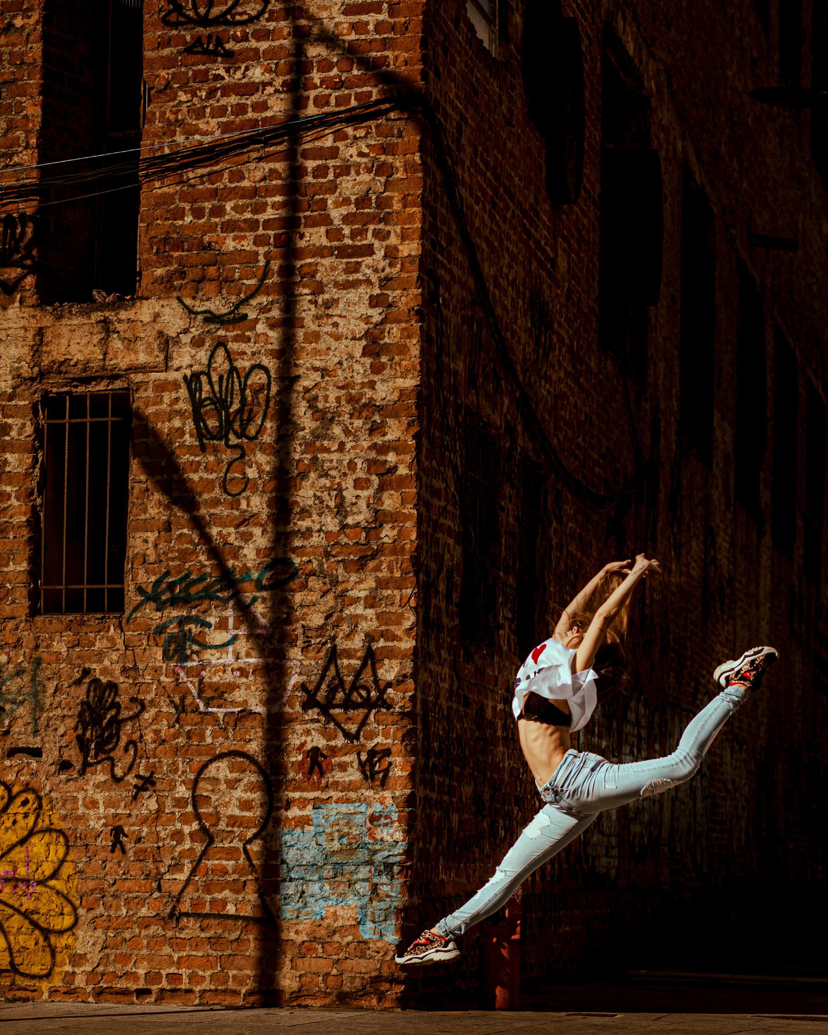 Woman Jumping Near Brick Building