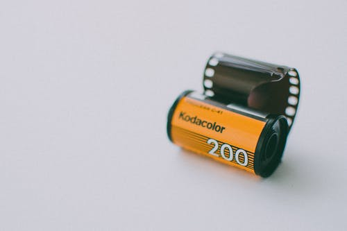 Roll of Kodak Gold Analogue Camera Film on a Light Blue Background