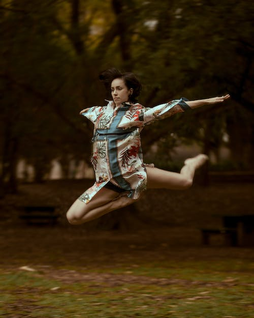 Selective Focus Photo of Jumping Woman Wearing Blue and White Cross-printed Top