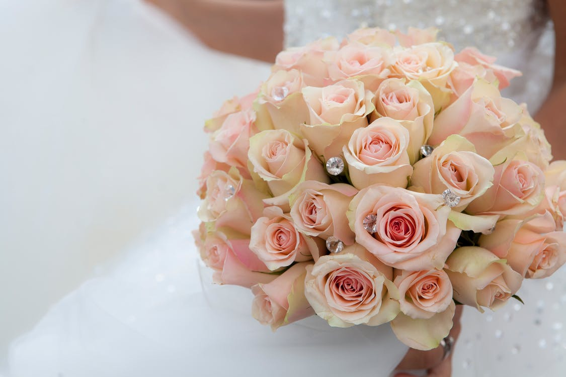 Selective Focus Photography of Woman Holding Pink Petaled Rose Arrangement