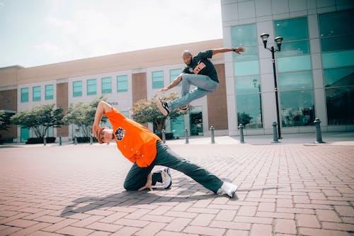 Two Men Dancing on Concrete Pavement