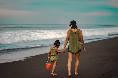 Back view Photo of Woman and Child Holding Hands While Walking on Beach