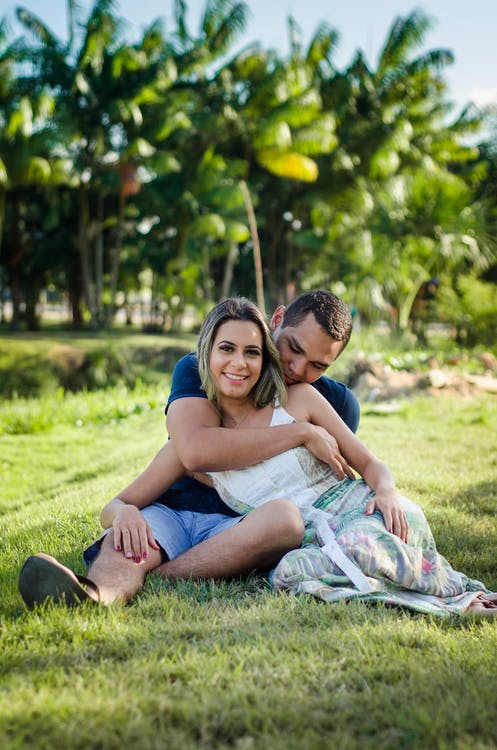 Photo of Man Hugging Woman While Siting on Green Grass