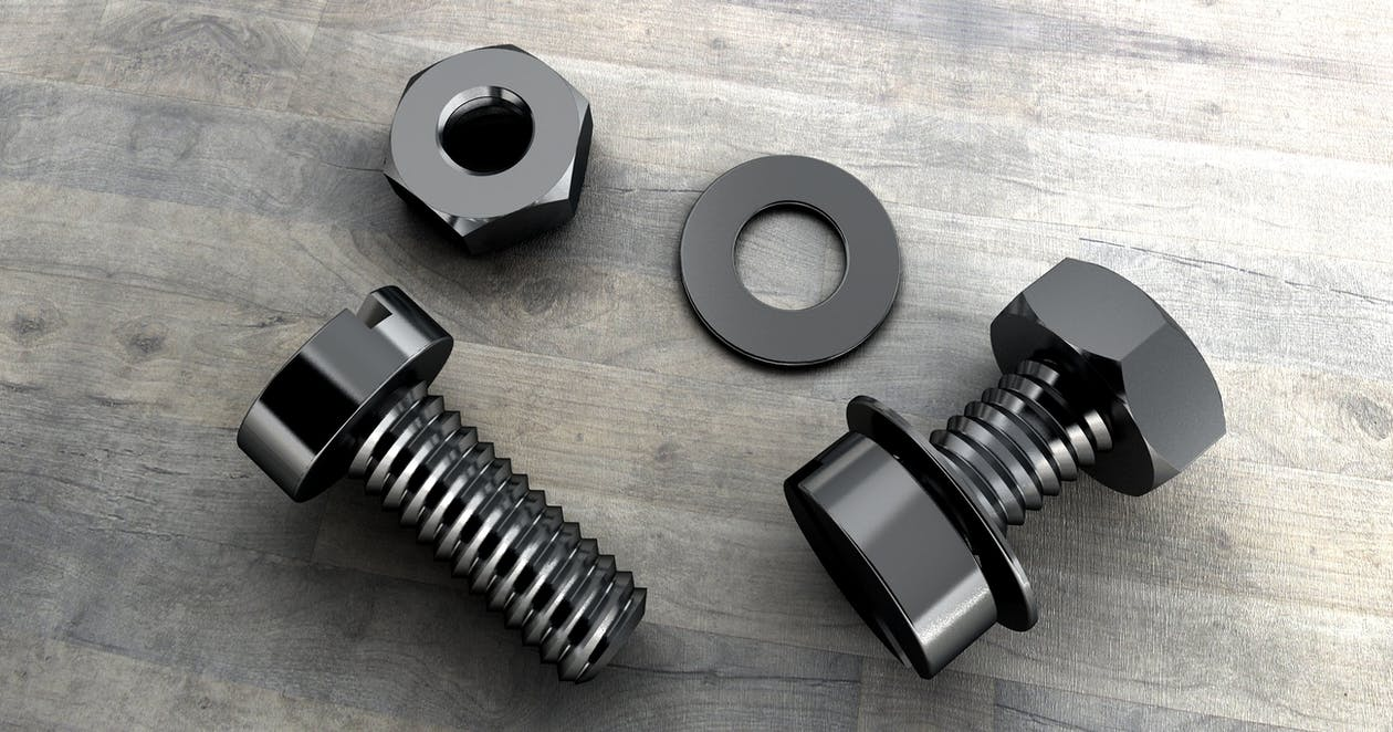 Two Black Metal Bolts on Gray Wooden Surface