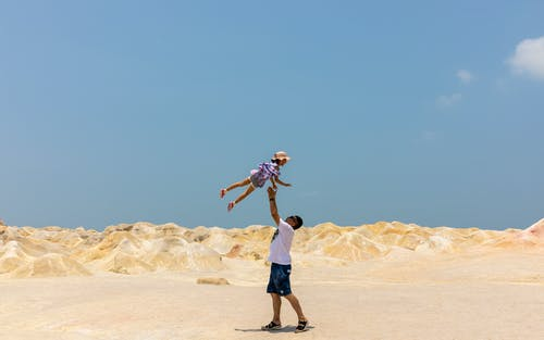 Man Lifting Girl Up While Standing on Sand