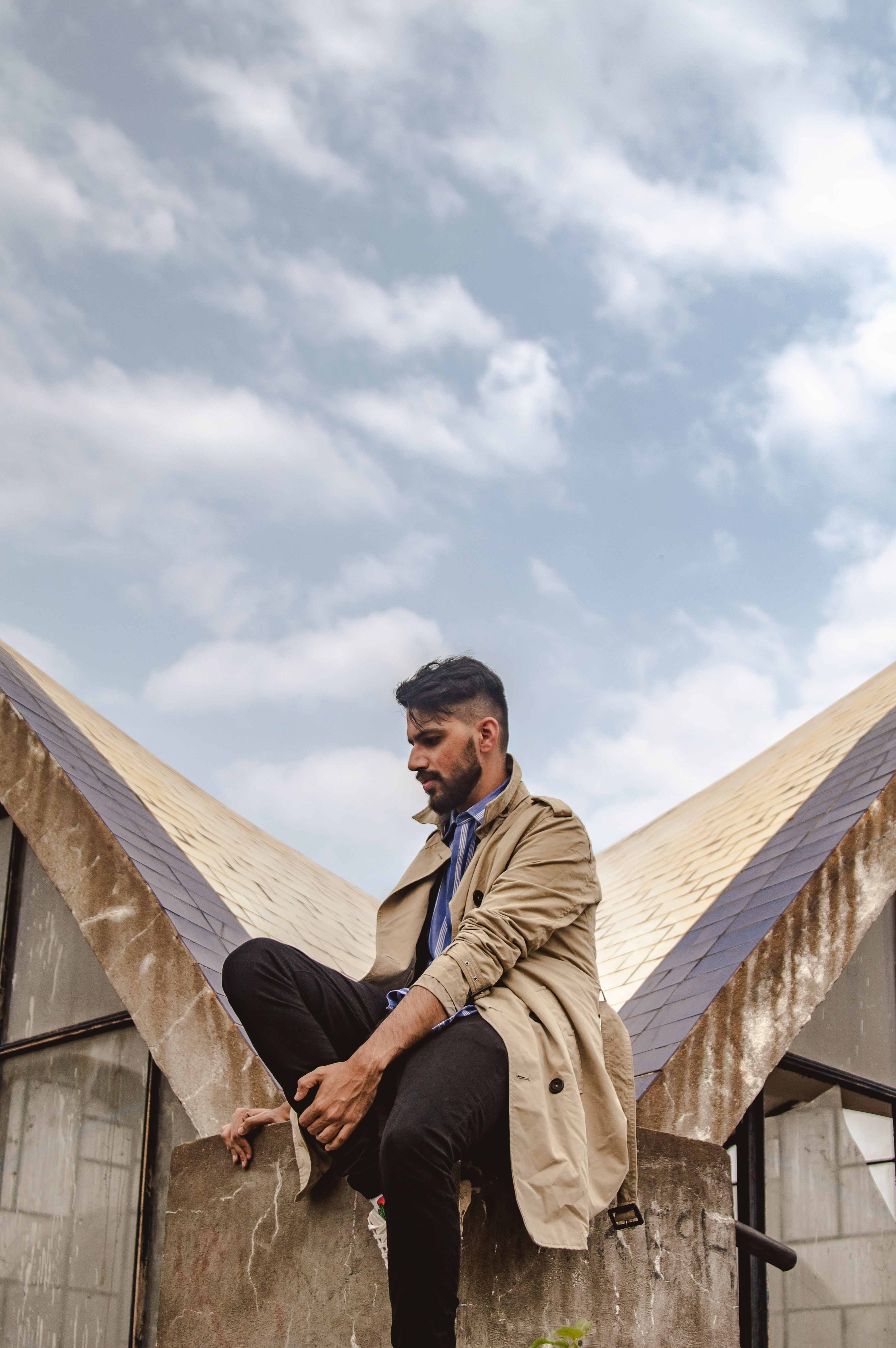 Man Sitting on Gray and Brown Roof Surface