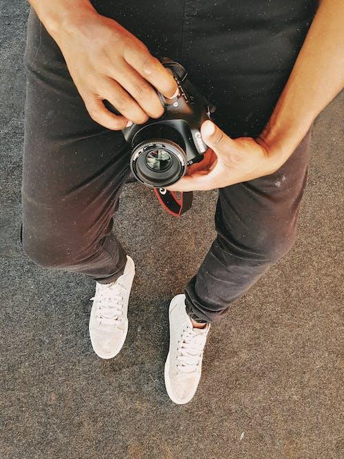 Fotobanka sbezplatnými fotkami na tému čierne nohavice, človek, digitálny fotoaparát, držanie