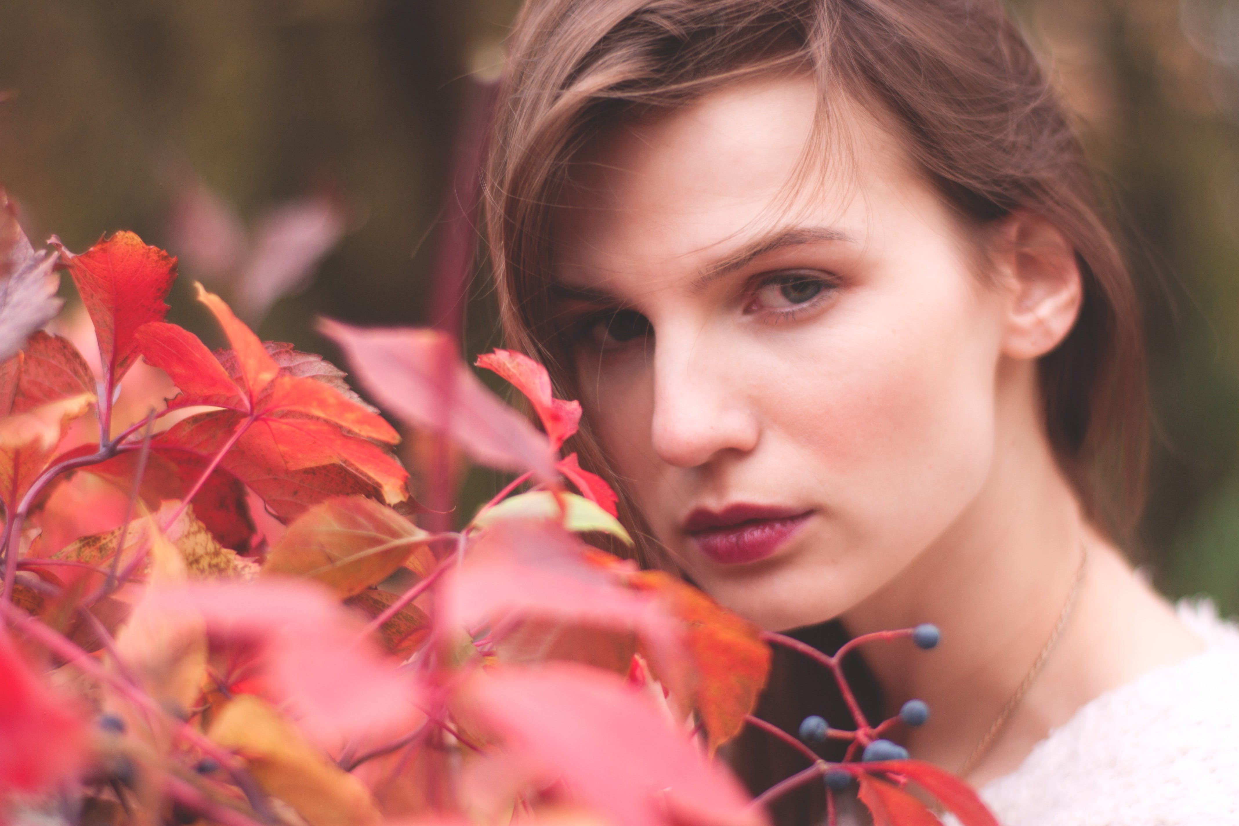 Woman Standing Near Red Leaf Plant