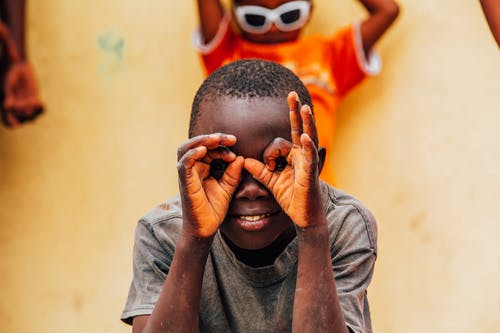 Photo of Boy Doing Hand Sign on His Face