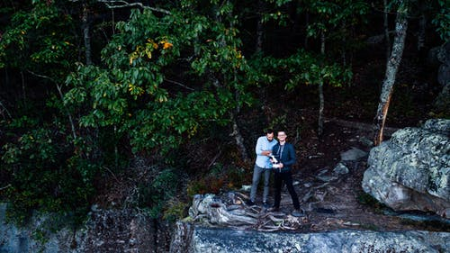 Two Men Standing Near Cliff