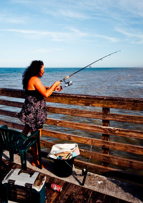 Woman Wearing Black and Gray Tube Top While Holding Fishing Rod