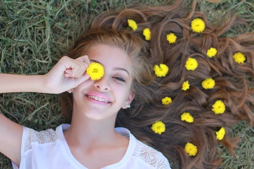Woman Lying on Grass and Holding Yellow Flower