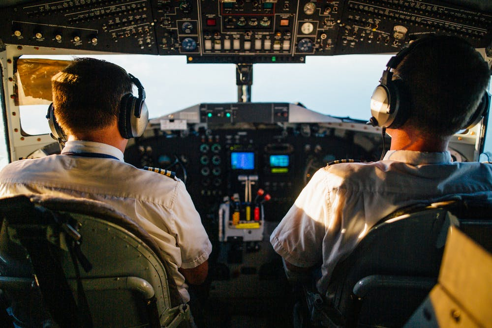 Two pilots flying an airplane. | Photo: Pexels